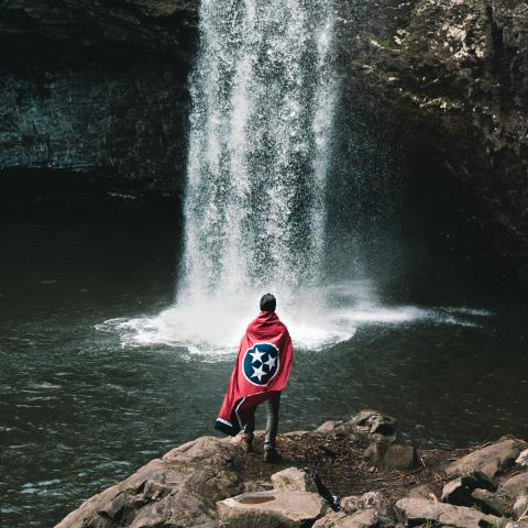 Man in front of Foster Falls with Tennessee state flag
