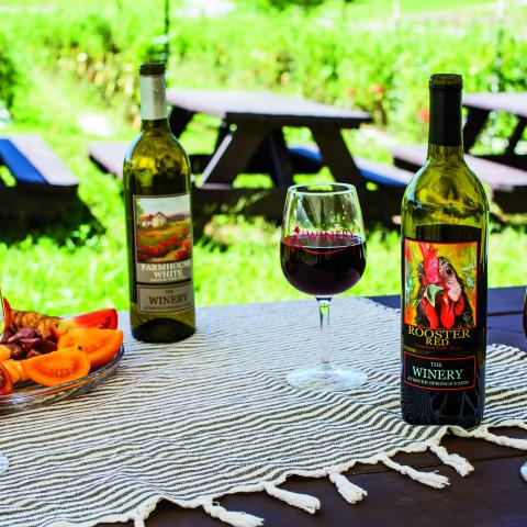 Two bottles of wine, a glass of red and white with a fruit platter on a fringed tablecloth at Winery at Seven Springs Farm